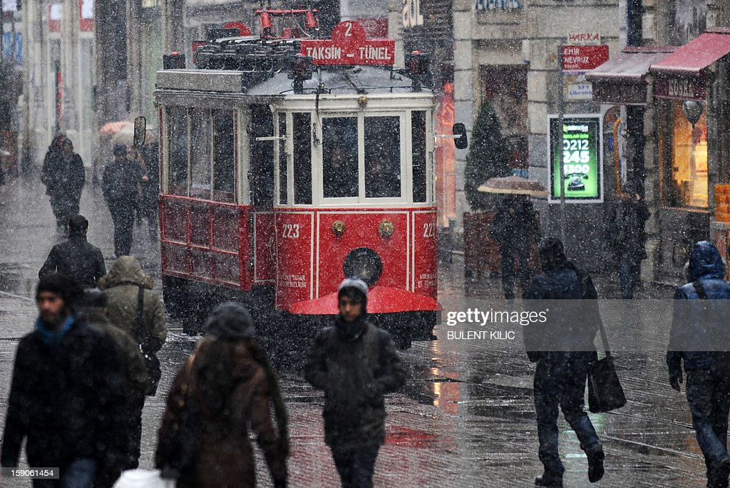 Snow falls as people walk on Istiklal avenue in Istanbul, on January 7, 2013. Heavy snowfall blanketed Turkey's commercial hub Istanbul, a city of 15 million, paralysing daily life, disrupting air traffic and land transport. Officials said the snow is expected to continue until late tomorrow, according to the weather forecast.