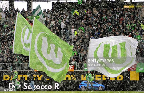 Snow falls as Wolfsburg flags are waved by fans next to the pitch ahead of the German first division Bundesliga football VfL Wolfsburg vs Borussia...