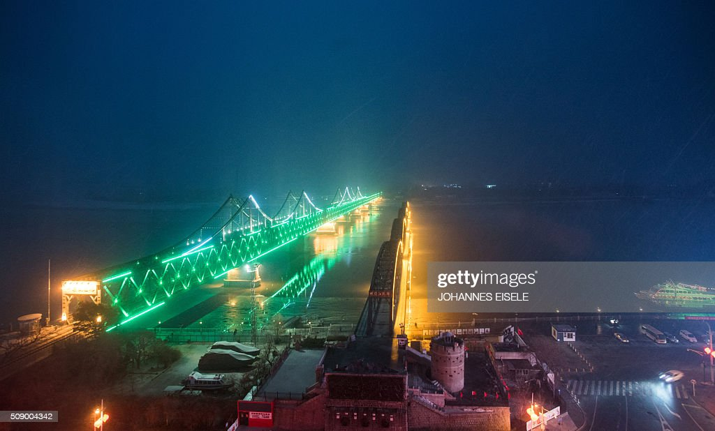 Snow falls over the bridge on the banks of the Yalu River at the Chinese border town of Dandong across from the North Korean town of Sinuiju on February 8, 2016. The UN Security Council strongly condemned North Korea's rocket launch on February 7 and agreed to move quickly to impose new sanctions that will punish Pyongyang for 'these dangerous and serious violations.' AFP PHOTO / JOHANNES EISELE / AFP / JOHANNES EISELE