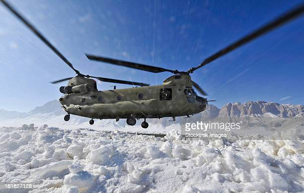 Snow flies up as a U.S. Army CH-47 Chinook helicopter prepares to land.