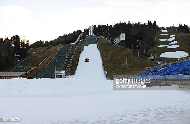 A snow groomer prepares the ski jump with artificial snow in GarmischPartenkirchen southern Germany on December 22 2015 The traditional Four hills...