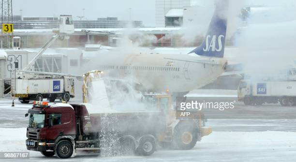 Snow is cleared from the tarmac between Terminal 3 and 4 while an SAS Boeing 737800 is being deiced at gate at Arlanda airport north of Stockholm on...