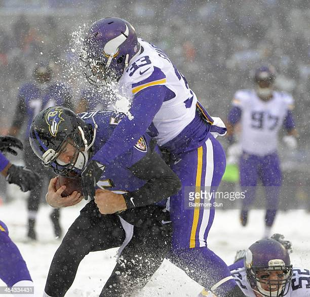 Snow kicks up from the collision as Baltimore Ravens quarterback Joe Flacco is hammered by Minnesota Vikings safety Jamarca Sanford after he gets a...