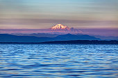 snow mountain at a misty sunset with sea water in the foreground