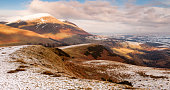 Snow covers the rolling hills of Latrigg and Blencathra mountain in the English Lake District.