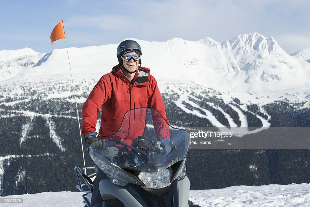 Snow patrol rescue worker riding snowmobile, mountains in background : Stock Photo