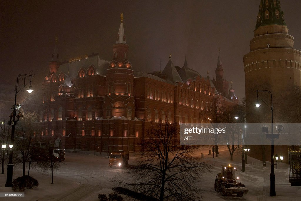 A snow plough clears the Manezhnaya Square just outside the Kremlin (R) in Moscow, late on March 24, 2013, with the State Historical Museum rising in the background (L). A snowstorm swept into Moscow yesterday as the temperatures in the Russian capital reached today -8 C (16 F), but due to high humidity and wind, weather experts said it would feel more like - 16 C (2 F). The snowfall that started yesterday was expected to continue into today, deluging the city with 28 to 35 centimeters of snow, the city media reported.
