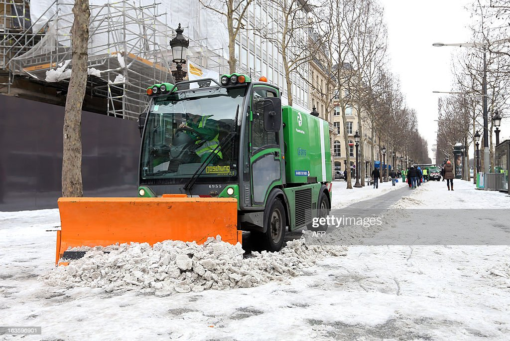 A snow plough clears the snow from a pavement on March 13, 2013 in Paris. Blizzard-like conditions, coming only eight days before the official start of spring, knocked out power to thousands of people in France and left motorists stranded in their cars.