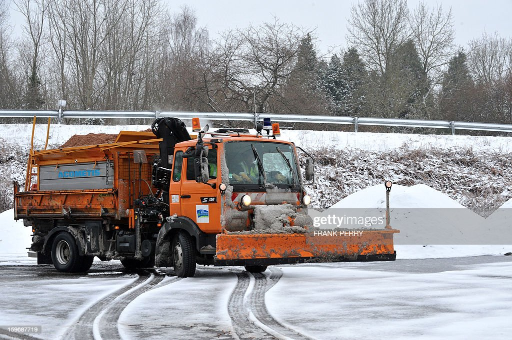 A snow plough drives on a ice covered road on January 18, 2013 near Vigneux-de-Bretagne, Brittany, western France. Thirty-seven French departments are under medium range (orange) alert due to the inclement weather. AFP PHOTO FRANK PERRY