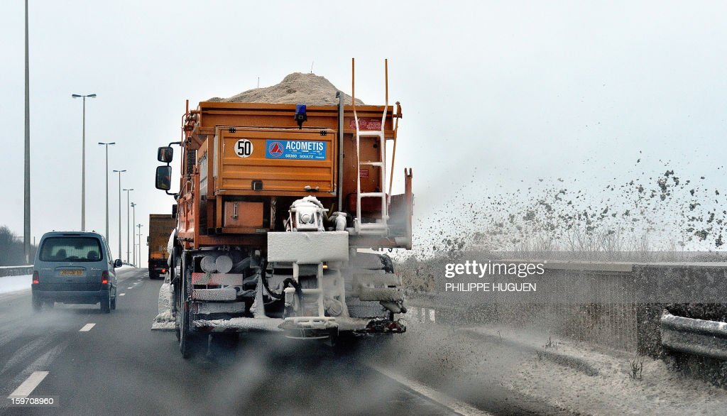 A snow plough drives on a snow covered road on January 19, 2013 near Boulogne-sur-Mer, northern France, after heavy snow falls.