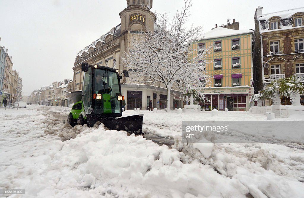 A snow plough removes the snow from the streets in Cherbourg following heavy snowfalls on March 12, 2013. More than 68,000 homes were without electricity in France and hundreds of people were trapped in their cars after a winter storm hit with heavy snow, officials and weather services said today. Overnight Monday nearly 500 cars were blocked near Cherbourg where snowdrifts piled up 60 centimetres (almost two feet) as winds reached 100 kilometres (more than 60 miles) an hour. AFP PHOTO / JEAN-PAUL BARBIER