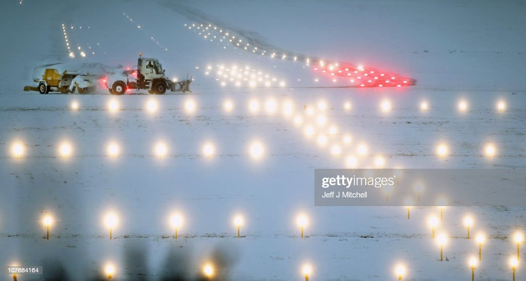 Snow ploughs work to clear snow and ice on one of the runways at Edinburgh Airport on December 19, 2010 in Edinburgh, Scotland. The United Kingdom is continuing to suffer heavy snowfall causing delays at many airports and closure of major roads.
