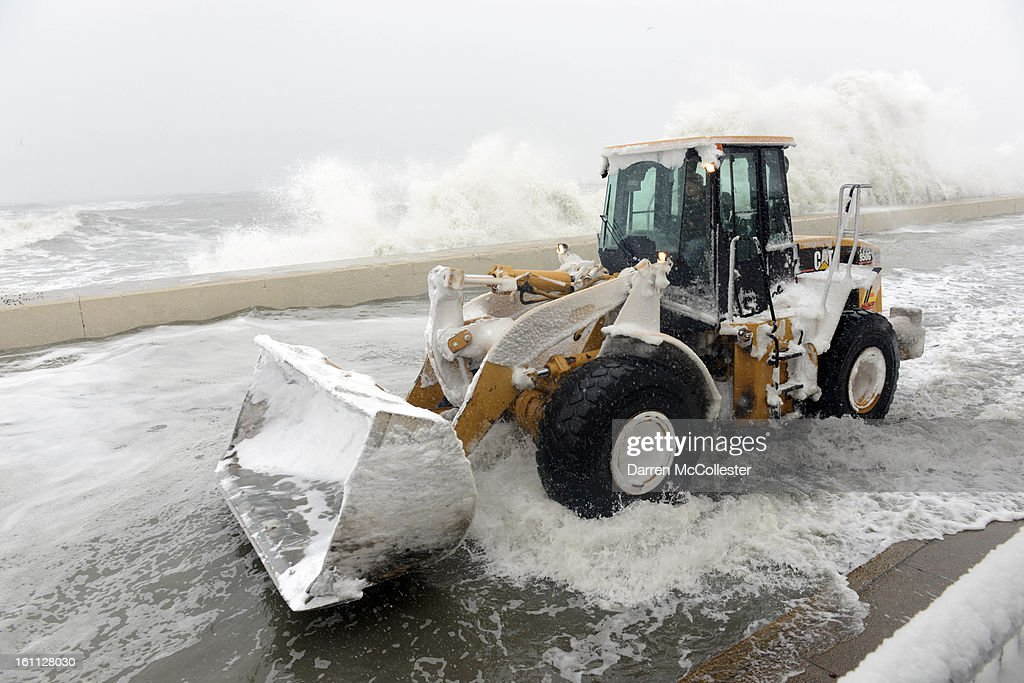 A snow plow goes down Winthrop Shore Drive as waves crash over the sea wall February 9, 2013 in Winthrop, Massachusetts. An overnight blizzard left one to two feet of snow in areas, and coastal flooding is expected as the storm lingers into the day.