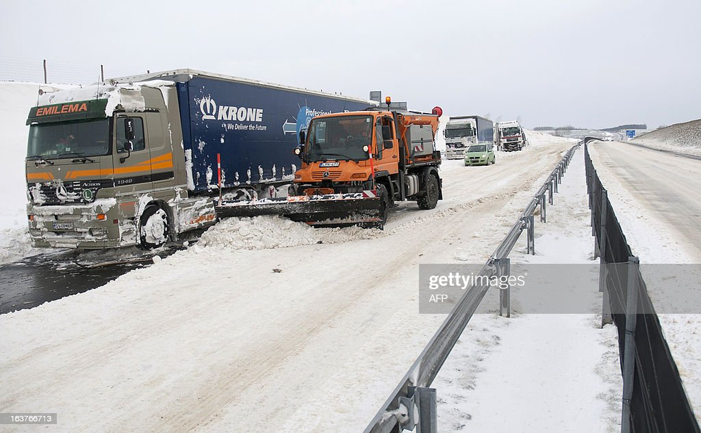 Snow plows clean the E71 motorway for immobilized trucks, nearby the Croatian, Slovenian and Hungarian borders on March 15, 2013 a day after a heavy snow storm hit the area. A cold snap that caused havoc elsewhere in Europe sent temperatures plunging and blanketed large parts of Hungary in snow, causing major transport problems and leaving tens of thousands without electricity. AFP PHOTO / SZILARD GERGELY