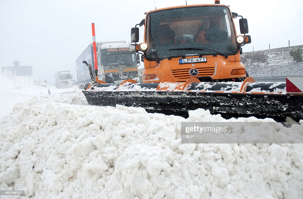 Snow plows clean the E71 motorway, nearby the Croatian, Slovenian and Hungarian borders on March 15, 2013 a day after a heavy snow storm hit the area. A cold snap that caused havoc elsewhere in Europe sent temperatures plunging and blanketed large parts of Hungary in snow, causing major transport problems and leaving tens of thousands without electricity.