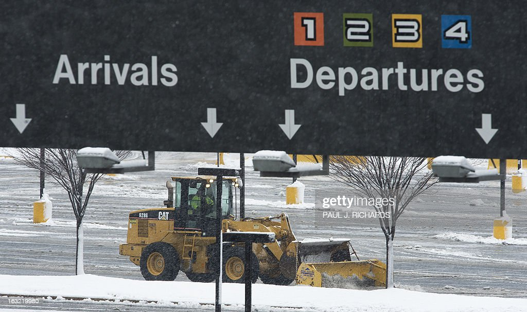 Snow removal equipment clears one of the parking lots at Dulles International Airport, March 6, 2013, in Sterling, Virginia, a few miles outside of Washington, DC . Federal offices and many schools have closed in preparation for a mix of snow, sleet and rain which could account for the area's largest winter storm in two years. AFP Photo/Paul J. Richards