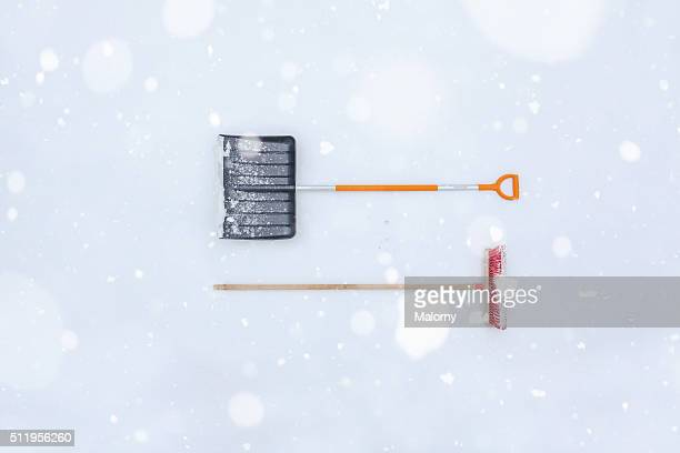 Snow shovel and broom in snow, during snowfall. View from above. Knolling. Super Still Life.