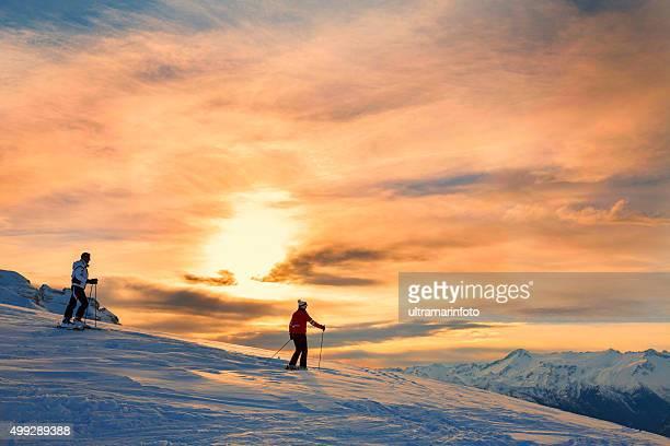 Neve, sciatori coppia godendo il bellissimo tramonto paesaggio invernale con montagne
