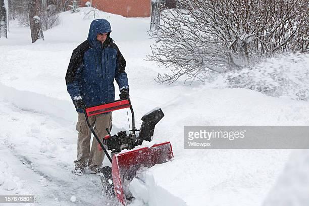 Sgombraneve giovane uomo sul vialetto in tempesta di neve Blizzard