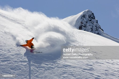 A snowboarder carving in powder