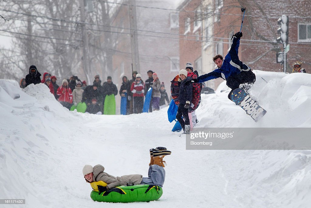 A snowboarder catches air as a resident sleds down the street after Winter Storm Nemo in Boston, Massachusetts, U.S., on Saturday, Feb. 9, 2013. More than two feet of snow fell on parts of the U.S. Northeast as high winds left hundreds of thousands of people in the region without power, closed highways and forced the cancellation of 4,700 flights. Photographer: Scott Eisen/Bloomberg via Getty Images
