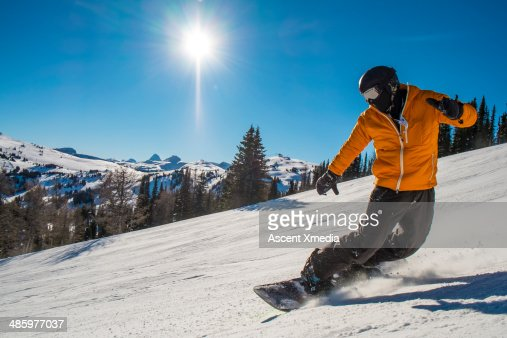 Snowboarder cranks turn on mountain slope