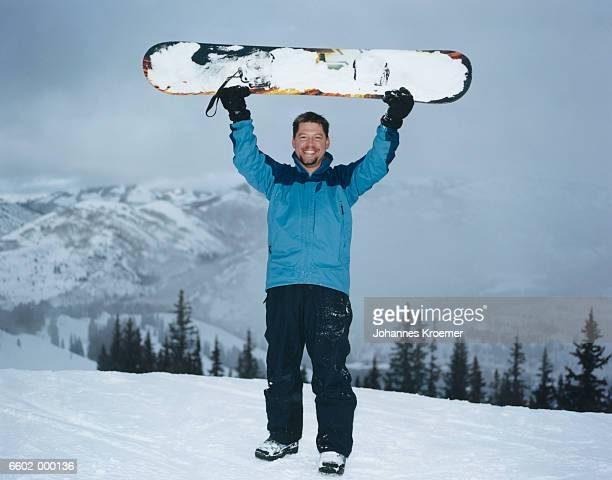 Snowboarder Holding Snowboard