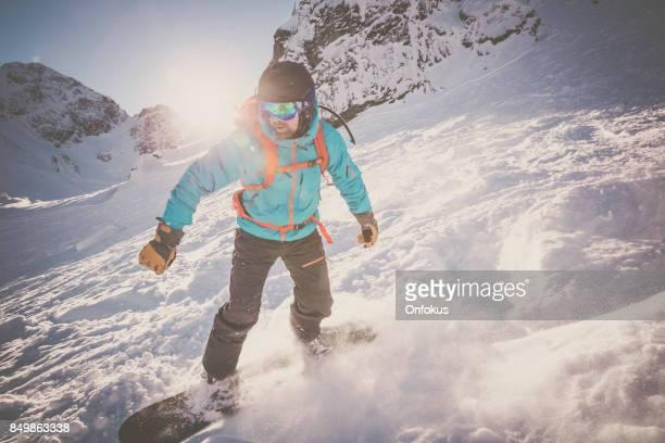 新雪パウダーのアクションでスノーボーダー