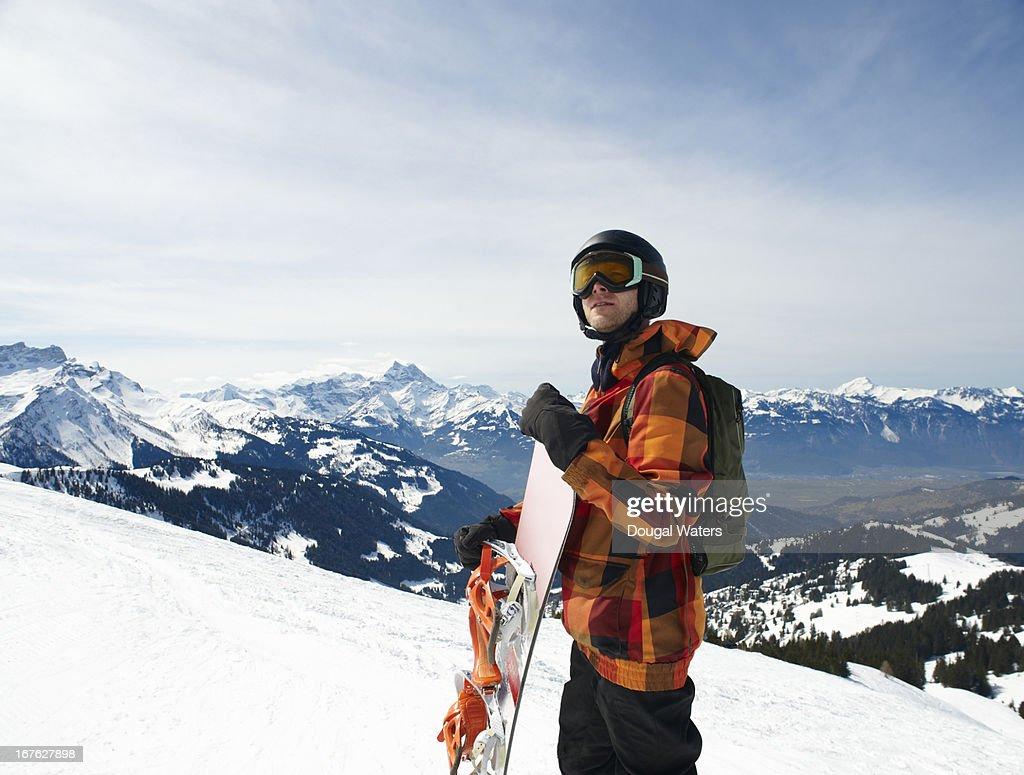 Snowboarder in ski wear in Swiss Alps.