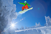 Snowboarder jumping against high mountains