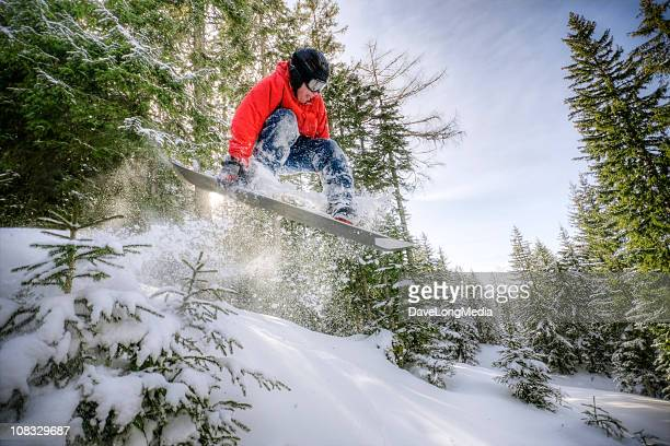 Snowboarder Jumping in Forest