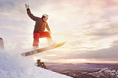 Snowboarder jumps against sunset sky and mountains