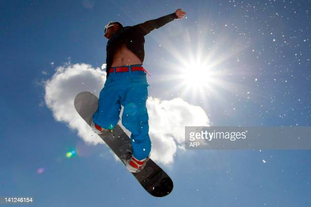 A snowboarder jumps and makes acrobatic figure in the snowpark in the Val d'Ese ski resort in Bastelica close to Ajaccio in the French Mediterranean...