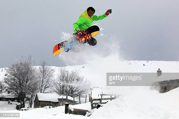 5A snowboarder jumps and makes acrobatic figures above a sheepfold in the Val d'Ese ski resort in Bastelica close to Ajaccio in the French...