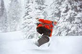 Snowboarder jumps at Sheregesh backcountry freeride off-piste ski resort. Winter sports