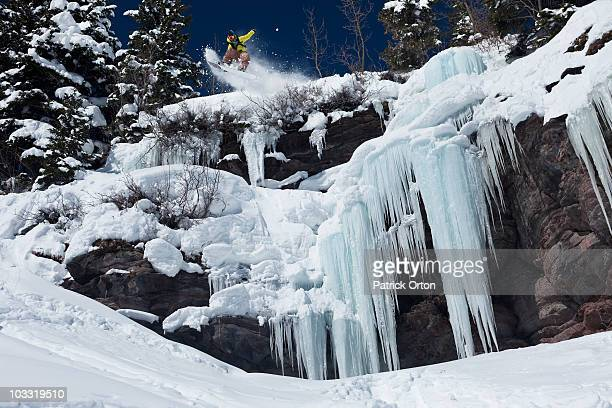 A snowboarder jumps off an ice waterfall cliff into powder in Colorado.