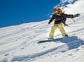 Young woman snowboarder in motion on snowboard in mountains on the slopes