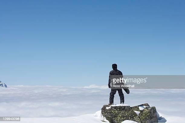 Snowboarder overlooking mountainside