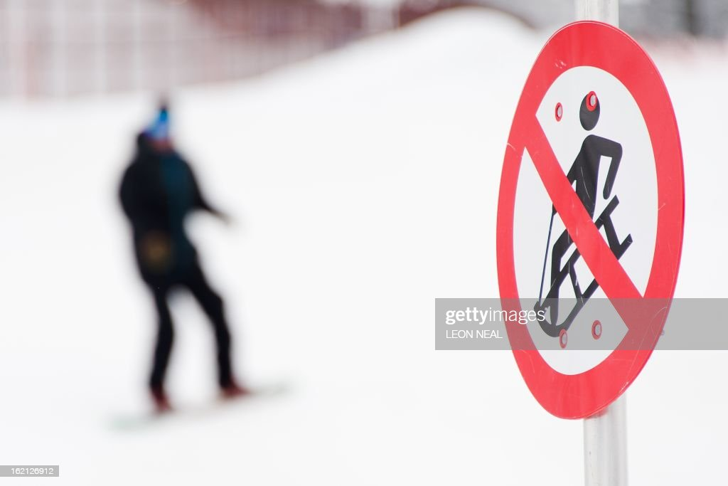 A snowboarder passes a 'No Sledging' sign on the Rosa Plateau above Rosa Khutor, one of the 2014 Winter Olympics venues, in the Black Sea city of Sochi on February 19, 2013. With a year to go until the Sochi 2014 Winter Games, construction work continues as tests events and World Championship competitions are underway.