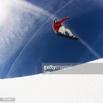 Snowboarder Performing a Toe Grab in Halfpipe