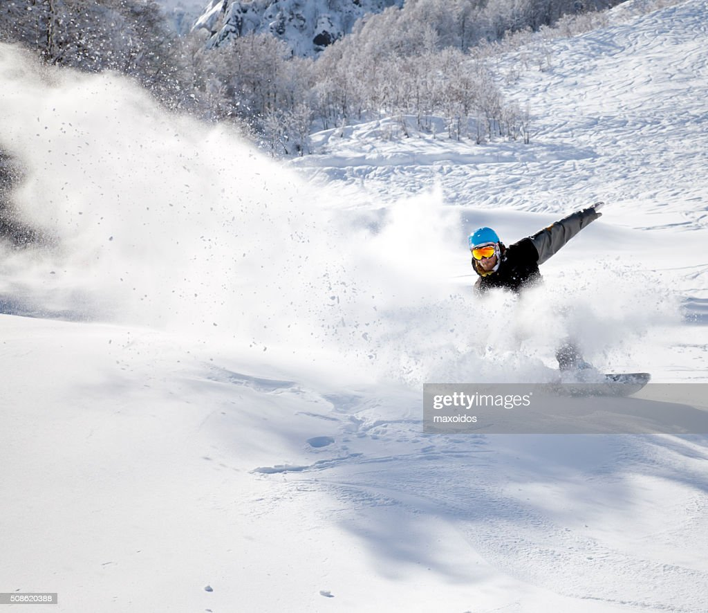 Snowboarder racing down : Stock Photo