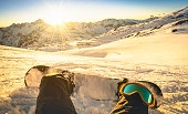 Snowboarder sitting on relax moment during sunset in public ski resort - Winter sport concept with person on top of the mountain ready to ride down - Legs view point with warm backlighting filter