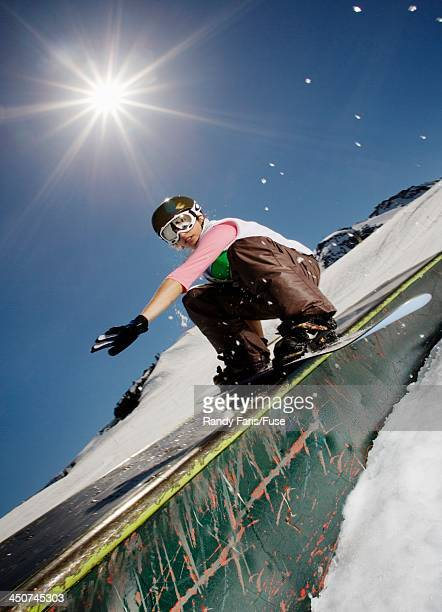 Snowboarder Sliding down Rail