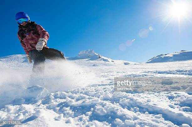 Snowboarder snowboarding down snowy mountains on sunny day.