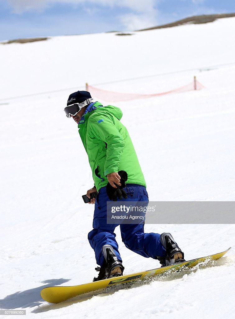 A snowboarder takes in late winter pistes at the ski resorts of Alborz mountain during a competition marking the end of the winter at Tochal ski resort north of the capital Tehran, Iran on May 3, 2016.