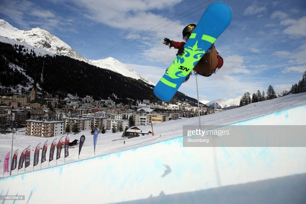 A snowboarder takes off from the slopes against the backdrop of Davos as they compete in the Audi AG sponsored snowboarders series in Davos, Switzerland, on Saturday, Jan. 18, 2014. Next week the business elite will gather in the Swiss Alps for the 44th annual meeting of the World Economic Forum (WEF) in Davos for the five day event which runs from Jan. 22-25. Photographer: Simon Dawson/Bloomberg via Getty Images
