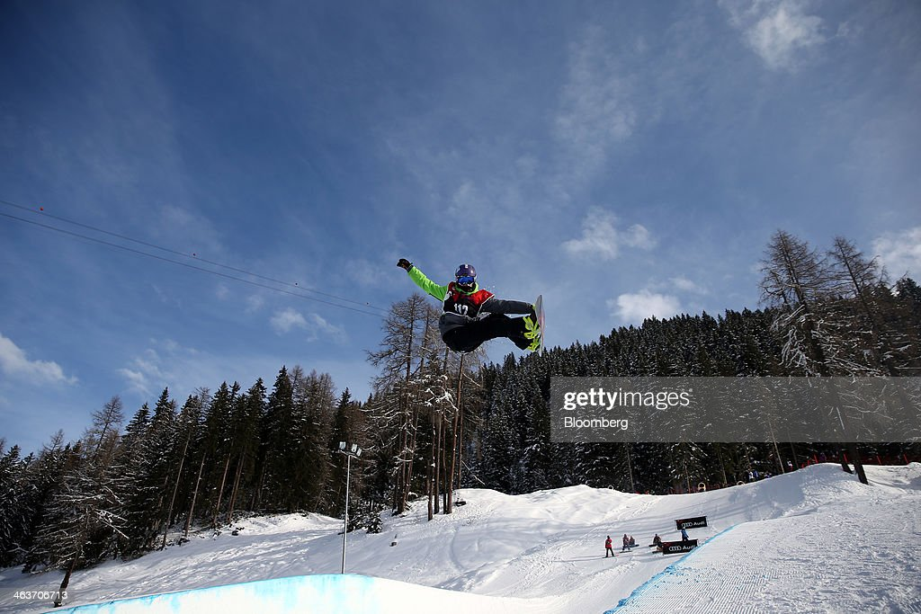 A snowboarder takes off from the slopes against the backdrop of the Jakobshorn mountain as they compete in the Audi AG sponsored snowboarders series in Davos, Switzerland, on Saturday, Jan. 18, 2014. Next week the business elite will gather in the Swiss Alps for the 44th annual meeting of the World Economic Forum (WEF) in Davos for the five day event which runs from Jan. 22-25. Photographer: Simon Dawson/Bloomberg via Getty Images