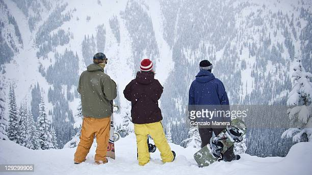Snowboarders admiring mountainside