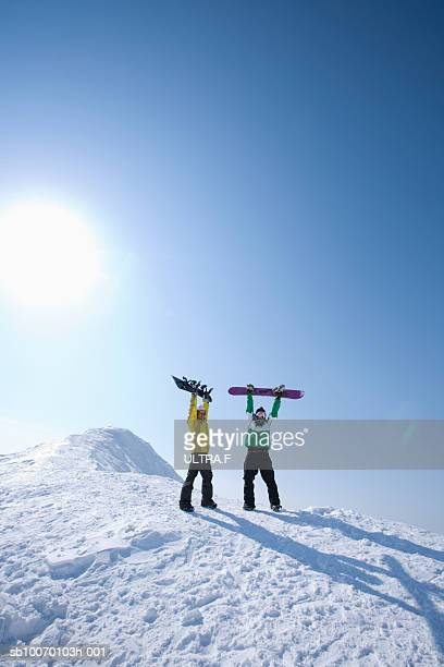 Snowboarders cheering on slope