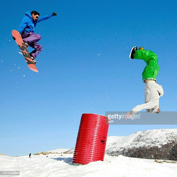 Snowboarders jump and make acrobatic figures in the snowpark in the Val d'Ese ski resort in Bastelica close to Ajaccio in the French Mediterranean...